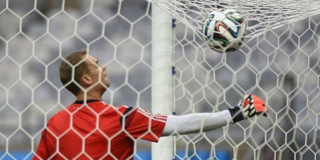 Germany's goalkeeper Manuel Neuer retrieves the ball from the goal net during a team training session...