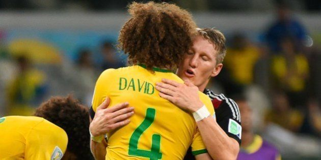 Germany's midfielder Bastian Schweinsteiger (R) hugs Brazil's defender and captain David Luiz after Germany...