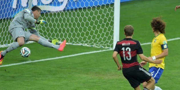 Germany's forward Thomas Mueller (C) scores their first goal during the semi-final football match between...