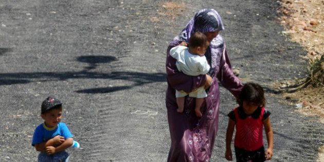 A Syrian refugee mother walks with children at a refugee camp in the Turkish border town of Yayladagi...