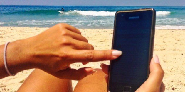 Womam typing on smartphone on the beach