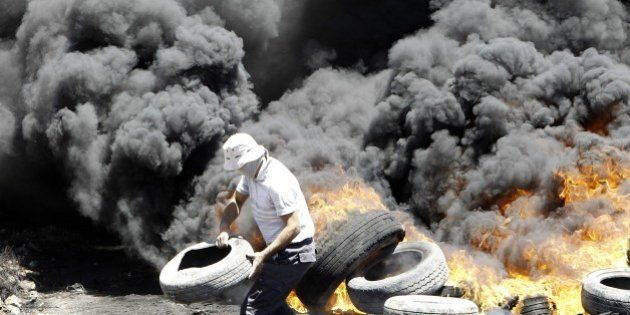A Palestinian burns tires during clashes with Israeli security forces following a protest in the village...
