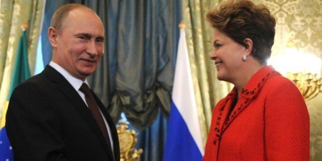 Russia's President Vladimir Putin welcome his Brazil's counterpart Dilma Rousseff (L) during their meeting...