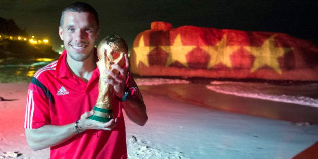 RIO DE JANEIRO, BRAZIL - JULY 13: Lukas Podolski of Germany poses with the World Cup trophy in front...