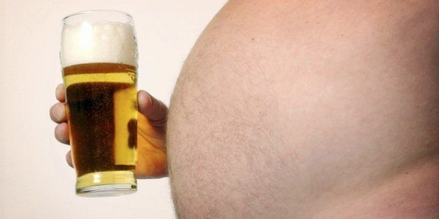 Man with large beer gut holding pint glass full of beer (Photo by Universal Images Group via Getty