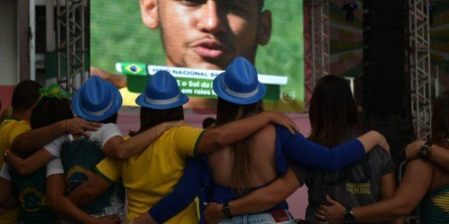 Brazil's fans look on a screen displaying Brazil's forward Neymar singing his national anthem as they...