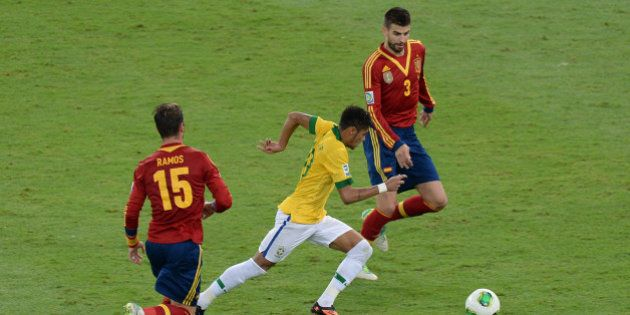 Brazil's forward Neymar (C) drives the ball past Spain's defenders Sergio Ramos (L) and Gerard Pique...