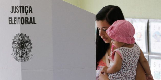 A woman holds a baby as she votes at an electronic voting booth during general elections at a school...