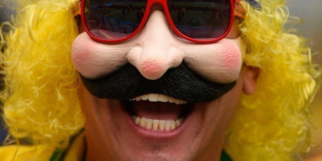 A fan of Brazil smiles before the semi-final football match between Brazil and Germany at The Mineirao...
