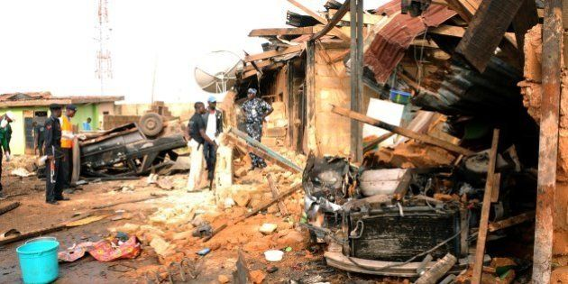 People looked at destroyed houses and vehicles at the site of a car bomb blast where football fans were...