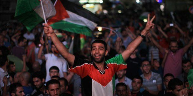 Palestinians celebrate in the West Bank city of Ramallah on May 30, 2014, after Palestine qualified for...