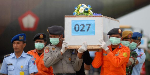 SURABAYA, INDONESIA - JANUARY 03: Indonesian soldiers carry coffins containing bodies of the AirAsia...