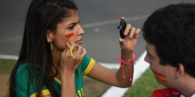 A woman paints her face with the colors of the Spanish team before a Group B football match between Spain...