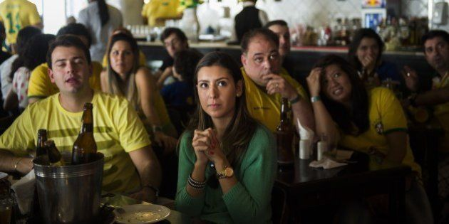 Brazilian supporters sitting in a bar in Mogi das Cruzes, Brazil, react as they watch on June 28, 2014...