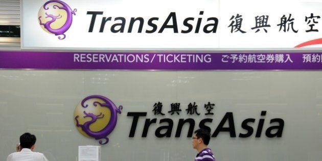 Local journalists wait in front of a TransAsia reservations desk at the Sungshan airport in Taipei on...