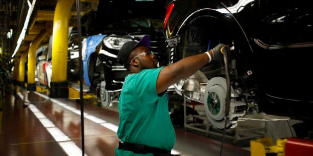 A worker uses a power tool on the wheel well of a Daimler AG Mercedes Benz M-Class vehicle at the company's...