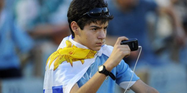 A Uruguayan national football team supporter takes a picture with his mobile phone before their Brazil...