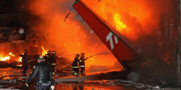 Sao Paulo, BRAZIL: Firefighters try to extiguish the fire around the wreckage of a TAM Brazilian airlines...