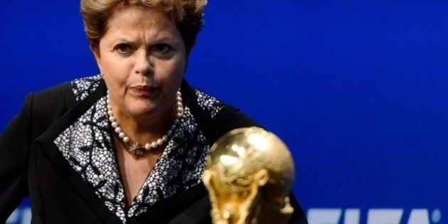 Brazilian President Dilma Rousseff gestures next to the FIFA World Cup trophy during a statement after...