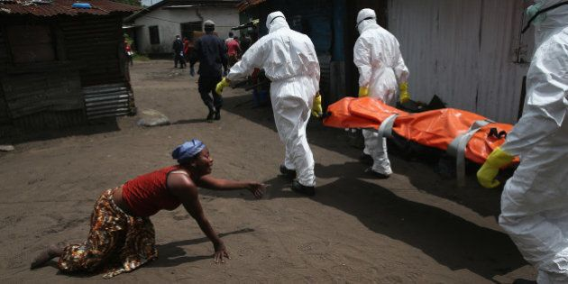 MONROVIA, LIBERIA - OCTOBER 10: A woman crawls towards the body of her sister as Ebola burial team members...