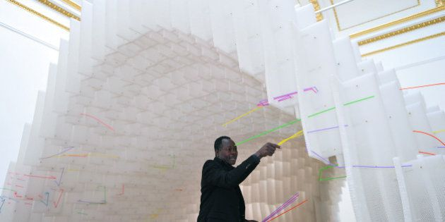Guinean-born German architect Diebedo Francis Kere poses next to his installation at the Royal Academy...