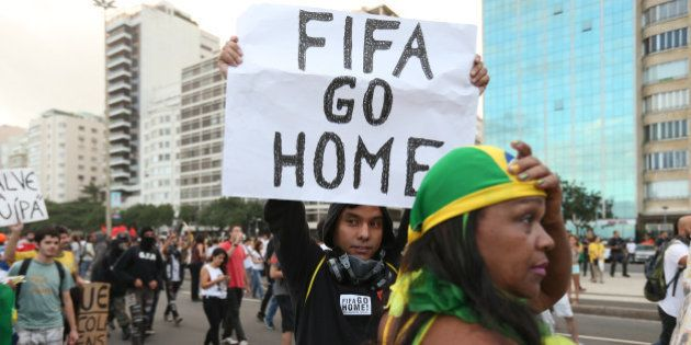 RIO DE JANEIRO, BRAZIL - JUNE 12: A protestor holds a 'FIFA Go Home' sign during an anti-World Cup demonstration...