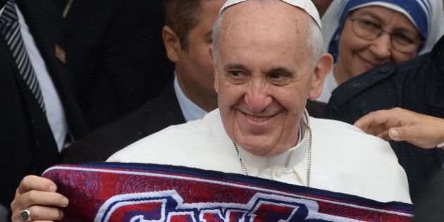 Pope Francis holds a scarf of Argentine football team San Lorenzo of which he is a fan, during his visit...