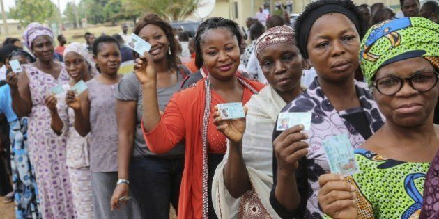 Women show their new electoral cards while queuing at a accreditation center in Abuja on March 28, 2015....