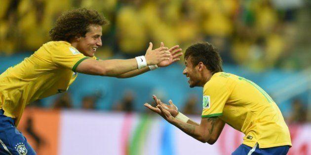Brazil's forward Neymar (R) celebrates with his teammate defender David Luiz after scoring a penalty...