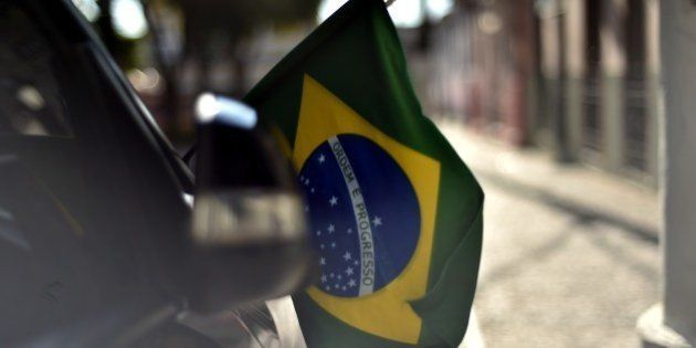 A supporters of the Brazilian national football team holds a Brazilian flag out of a car window in Itu...