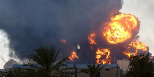 Smoke billows from a petrol depot that has been set ablaze following clashes between rival militias near...