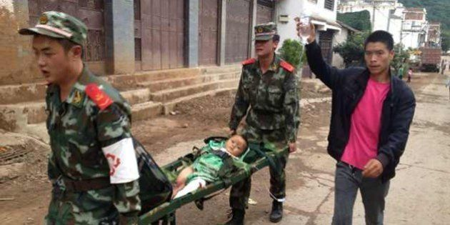 Rescuers carry an injuried child on a stretcher after a 6.1 magnitude earthquake hit the area in Ludian...