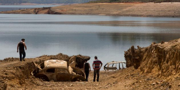 People walk around cars that emerged from the Atibainha dam, which is part of the Cantareira System,...