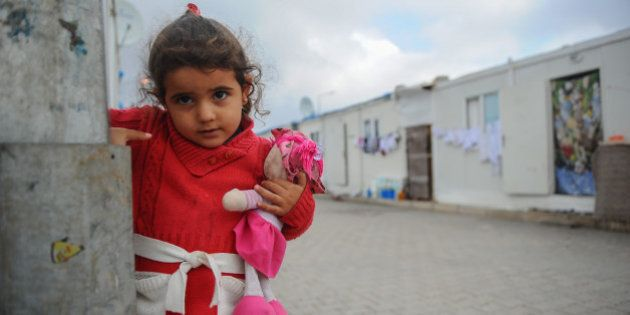 KILIS, TURKEY - JANUARY 22: A little girl with her baby doll poses at the Oncupinar Container city including...