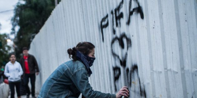 SAO PAULO, BRAZIL - JUNE 19: A member of the MPL 'Free Pass Movement' sprays graffiti during a protest...
