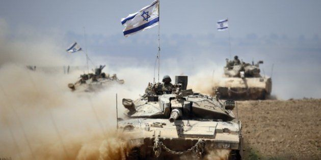 Israeli Merkava tanks roll near the border between Israel and the Gaza Strip as they return from the...