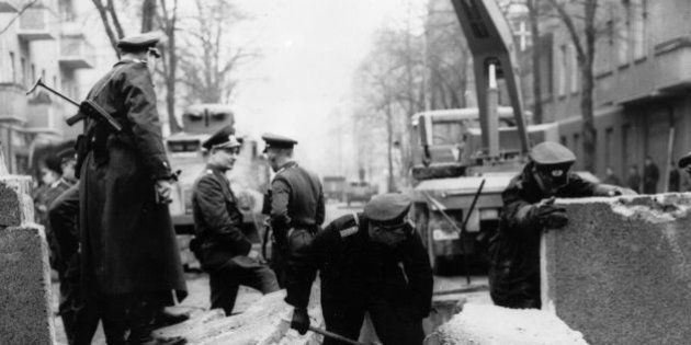 Officers inspecting the damage to the Berlin Wall, East Germany, and making preparations for its repair,...