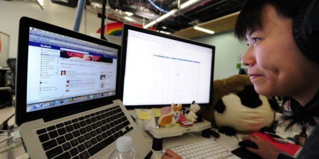 Facebook User Operations team member Kristie Chow checks a page of the number one social networking website...