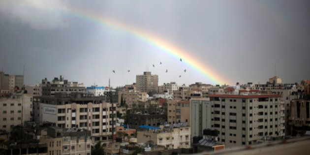 A rainbow shines over Gaza City following heavy rainfall on December 12, 2013 as a winter weather front...