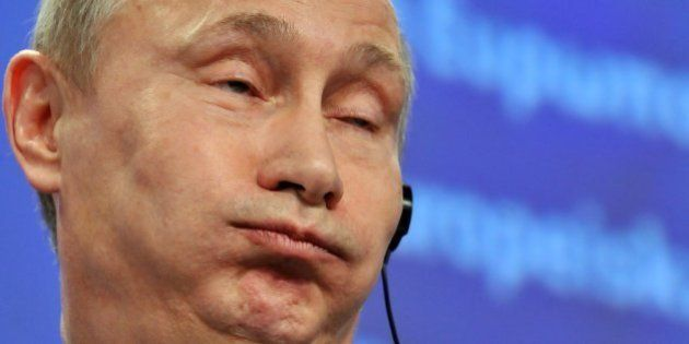 Russian Prime Minister Vladimir Putin makes a face during a joint press conference with European Commission...
