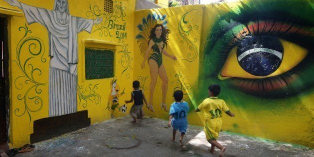Young Indian children in Brazil (R) and Argentina (C) football attire play in front of wall graffiti...
