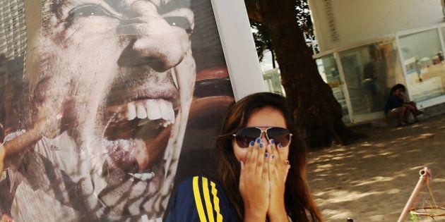 RIO DE JANEIRO, BRAZIL - JUNE 26: A woman takes a photo next to an advertisement featuring Uruguay's...