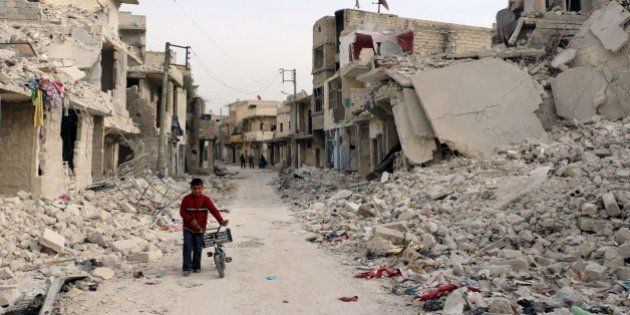 A Syrian boy walks with his bicycle in the devastated Sukari district in the northern city of Aleppo...