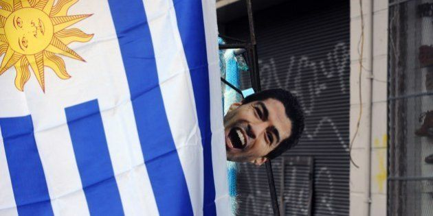 A mask of Luis Suarez hangs from a Uruguayan flag during the live broadcasting of the FIFA World Cup...