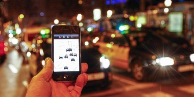 The Uber app is seen on a smartphone past cabs passing on Paseo de Gracia in Barcelona, on December 9,...