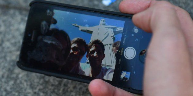 Tourists use a moblie telephone to photograph themselves with the Christ the Redeemer is seen on top...