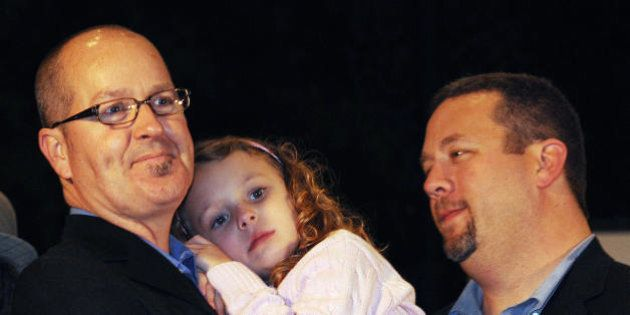 Shelby Barrett-Whitmore -5, hugs her fathers Toby Barrett (L) and Joe Whitmore (R) during a gay rights...