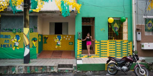 MANAUS, BRAZIL - JUNE 16: A girl looks out from a house decorated to celebrate the 2014 FIFA World Cup...