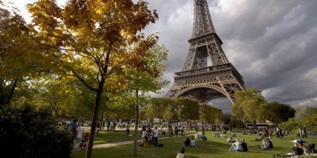 People enjoy sunbathing and relaxing by the Eiffel Tower on October 19, 2014 in Paris. Record hot weather...