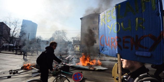 FRANKFURT AM MAIN, GERMANY - MARCH 18: Activists beside a burning barricade participate in a demonstration...